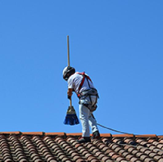 Un technicien nettoyant une toiture