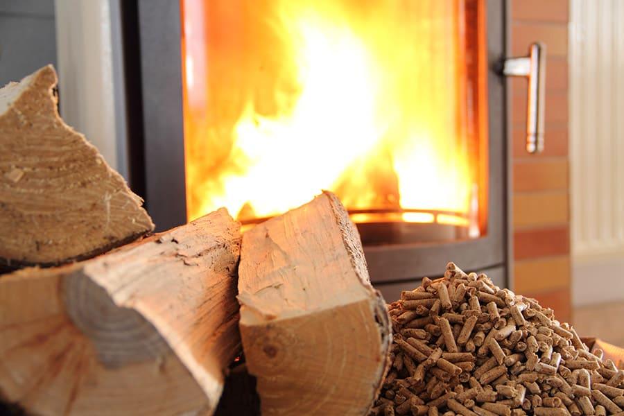 Des buches de bois et granulés devant un poêle