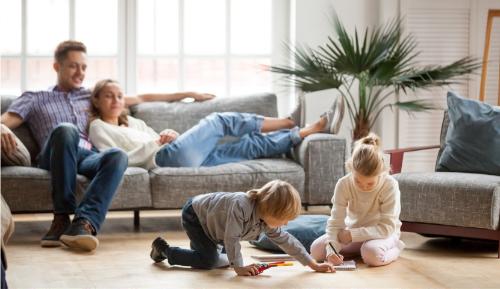 Une famille dans un salon, le couple sur le canapé regarde 2 enfants jouer.