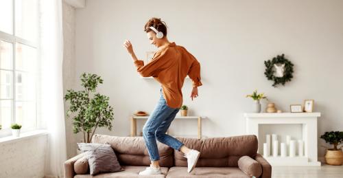 Une jeune femme danse debout sur son canapé.