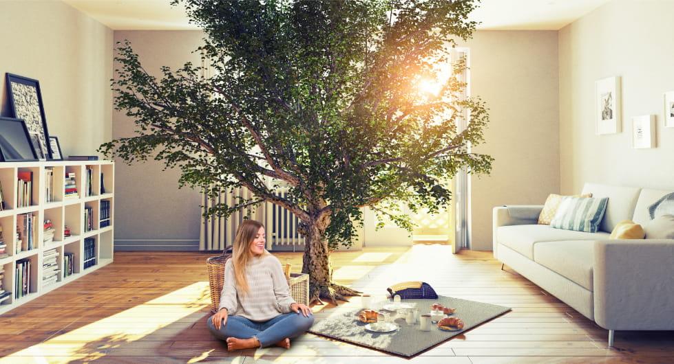 Une femme assise en tailleur dans son salon devant un arbre vert