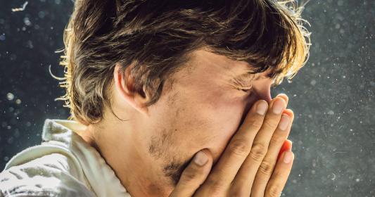 Un homme allergique éternu et se tien le nez.